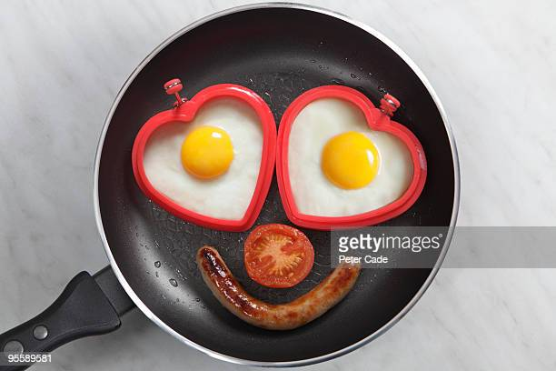 breakfast with heart shapped eggs in pan