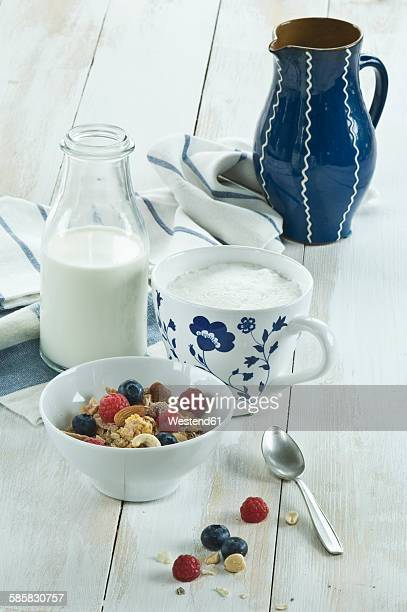 Breakfast with muesli and fruits, cappuchino and bottle of milk