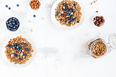 Breakfast with muesli, blueberry, nuts on white background. Healthy food concept. Flat lay, top view, copy space