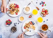 Flat lay with scotch pancakes in flower form, berries and honey with human hands. Healthy breakfast concept. Women eating together, top view.