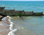 Breakwater groynes on a beach with waves