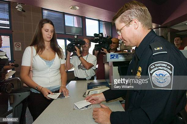 Breanna Hackenberry a US goverment employee watches as her new visa card is passed over a radio sensor by a US Customs agent as she returns to the US...