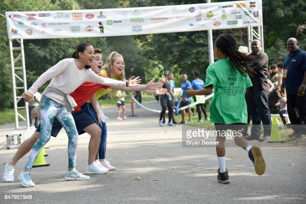 Breanna Yde Ricardo Hurtado and Jade Pettyjohn cheer on runners at Nickelodeon's Worldwide Day Of Play Celebration at the Nethermead in Prospect Park...