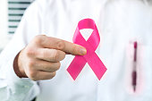 Breast cancer awareness concept. Doctor holding pink ribbon.