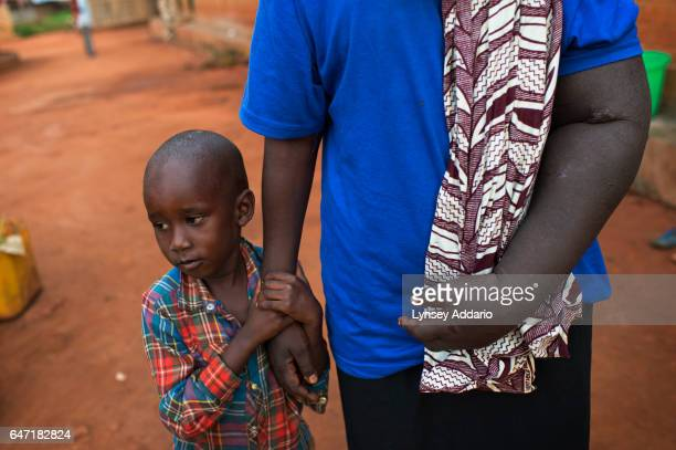 Breast Cancer patient Jessy Acen from Gulu stands with one of her sons Jered Kakanyero in Pece Vanguard on the outskirts of Gulu Uganda July 23 2013...