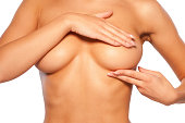 Cropped image of young shirtless woman examining her breasts while standing isolated on white