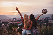 Two awesome girls cheering life in front of the sunset