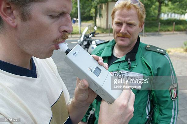 Breathalyzer test Man blowing into an alcohol measuring device during a police control