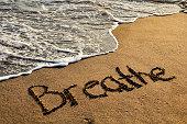 Word breathe on sunset beach