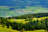 Breathtaking landscape of mountains, forests and small Bavarian villages in the distance. Scenic view of Bavarian Alps with majestic mountains in the background. Bavaria, Germany.