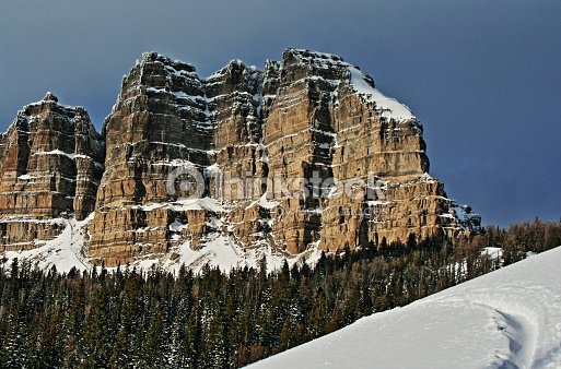 Breccia Peak And Cliffs In Winter Next To Snowmobile Tracks Stock