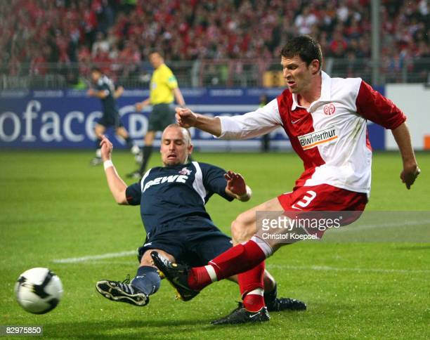 Brecko of Koeln tackles Peter van der Heyden of Mainz during the DFB Cup second leg match between FSV Mainz 05 and 1 FC Koeln at the stadium am...