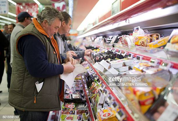 Breeders inspect the meat sold in a supermarket of Nantes western France on December 16 2015 to protest against the low sales prices of their...