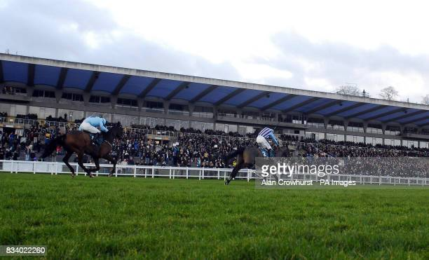 Breedsbreeze lead on the run in to win The Anglo Irish Bank Tolworth Hurdle from Deep Purple and Paul Moloney at Sandown Park Racecourse Surrey
