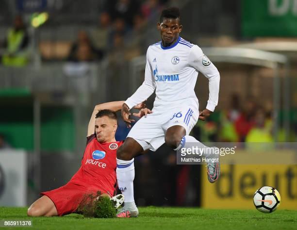 Breel Embolo of Schalke is challenged by Sebastian Mrowca of SV Wehen Wiesbaden during the DFB Cup match between SV Wehen Wiesbaden and FC Schalke 04...