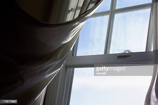 breeze blowing a curtain through an open window