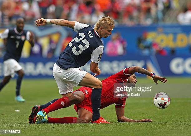 Brek Shea of the United States runs over Gabriel Gomez of Panama during the CONCACAF Gold Cup final match at Soldier Field on July 28 2013 in Chicago...