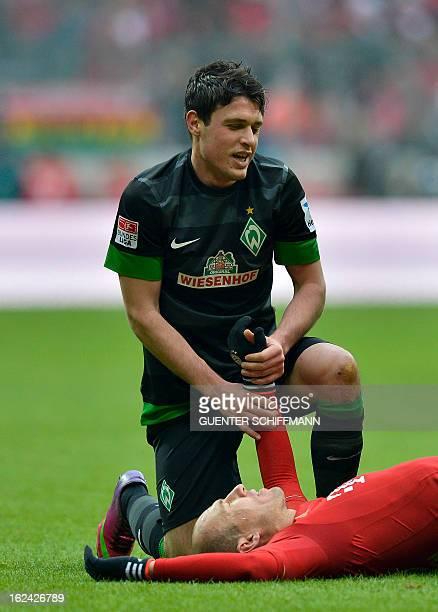 Bremen's Austrian midfielder Zlatko Junuzovic helps Bayern Munich's Dutch midfielder Arjen Robben to get up during the German first division...