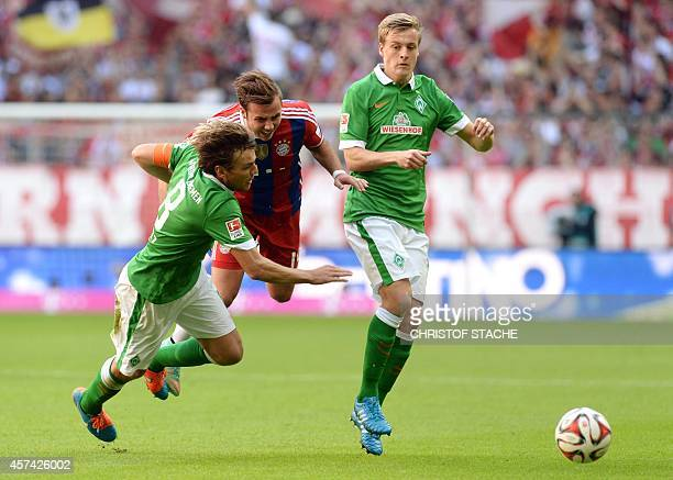 Bremen's defender Clemens Fritz Bayern Munich's midfielder Mario Goetze and Bremen's midfielder Felix Kroos challenge for the ball during the German...