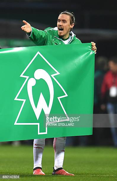 Bremen's midfielder Max Kruse holds up a banner wishing the fans a Happy Christmas after the German first division Bundesliga football match Werder...
