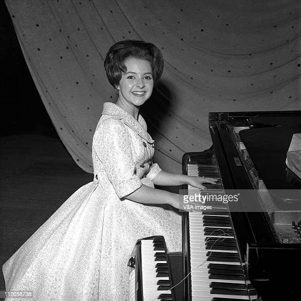 Brenda Lee posed backstage playing piano 1960