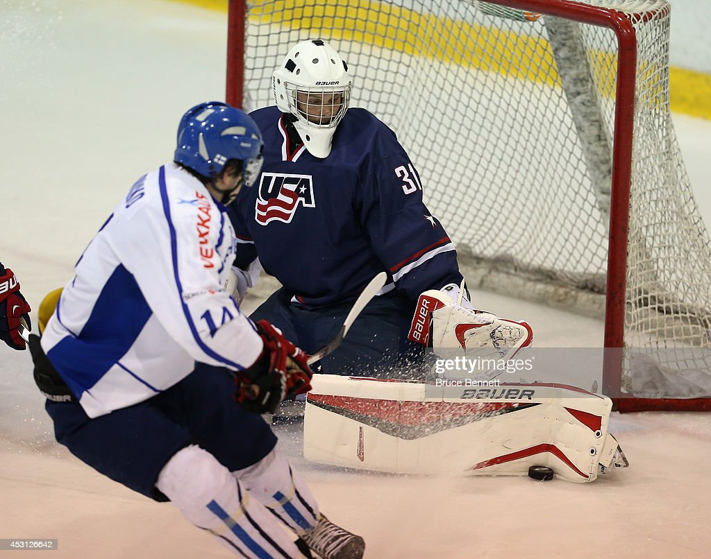 Brendan Burke #31 of USA Blue makes the third period save on Juho Lammikko #14 of Team Finland during the 2014 USA Hockey Junior Evaluation Camp at the Lake Placid Olympic Center on August 3, 2014 in Lake Placid, New York. USA Blue defeated Team Finland 2-1.