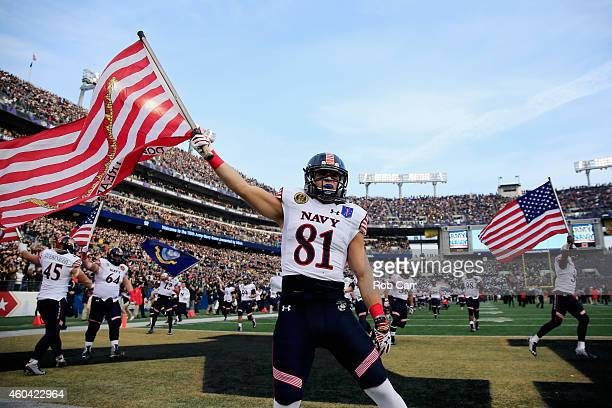 Brendan Dudeck of the Navy Midshipmen carries the American flag on the field before the start of their game against the Army Black Knights at MT Bank...