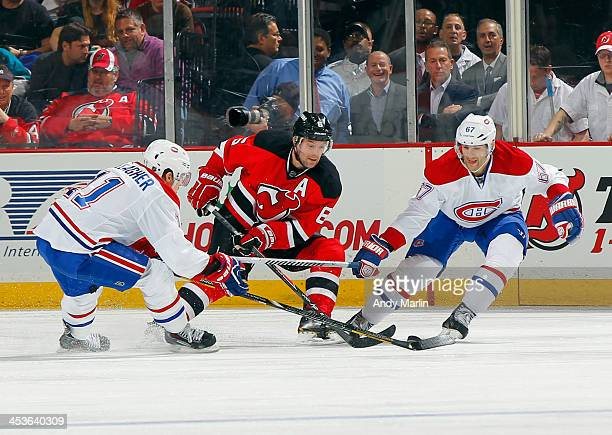 Brendan Gallagher and Max Pacioretty of the Montreal Canadiens and Andy Greene of the New Jersey Devils battle for a loose puck during the game at...