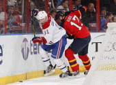 Brendan Gallagher of the Montreal Canadiens and Filip Kuba of the Florida Panthers skate after a loose puck at the BBT Center on March 10 2013 in...