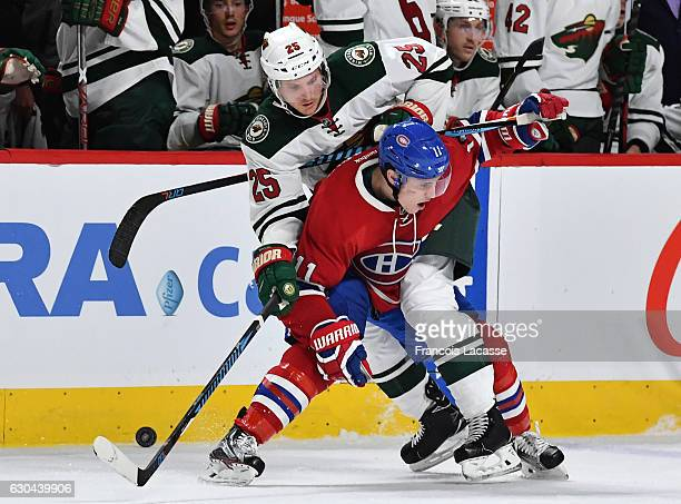 Brendan Gallagher of the Montreal Canadiens and Jonas Brodin of the Minnesota Wild fight for the puck in the NHL game at the Bell Centre on December...