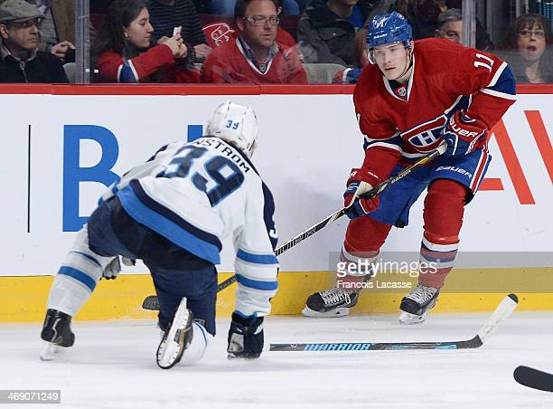 Brendan Gallagher of the Montreal Canadiens controls the puck while being challenged by Tobias Enstrom of the Winnipeg Jets during the NHL game on...