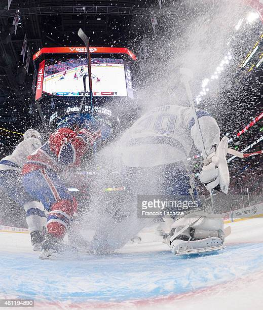 Brendan Gallagher of the Montreal Canadiens gives goalie Ben Bishop of the Tampa Bay Lightning a spray of ice as he follows the play in the NHL game...