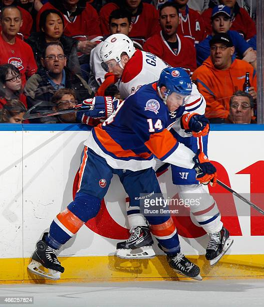 Brendan Gallagher of the Montreal Canadiens is hit into the boards by Thomas Hickey of the New York Islanders during the first period at the Nassau...