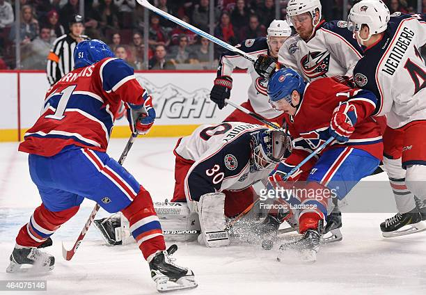 Brendan Gallagher of the Montreal Canadiens looks for the puck to shoot on goaltender Curtis Mcelhinney while Alexander Wennbergs and James...