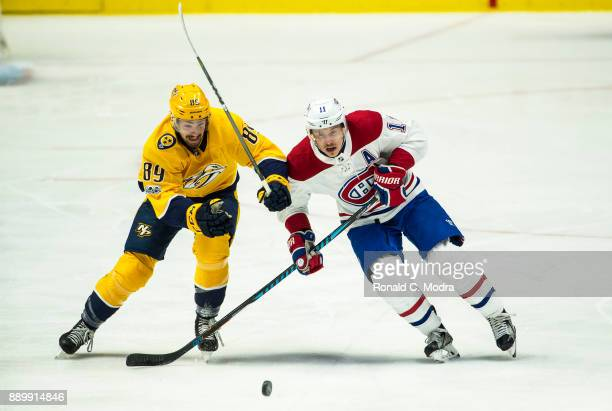 Brendan Gallagher of the Montreal Canadiens skates as Frederick Gaudreau of the Nashville Predators chases during an NHL game at Bridgestone Arena on...
