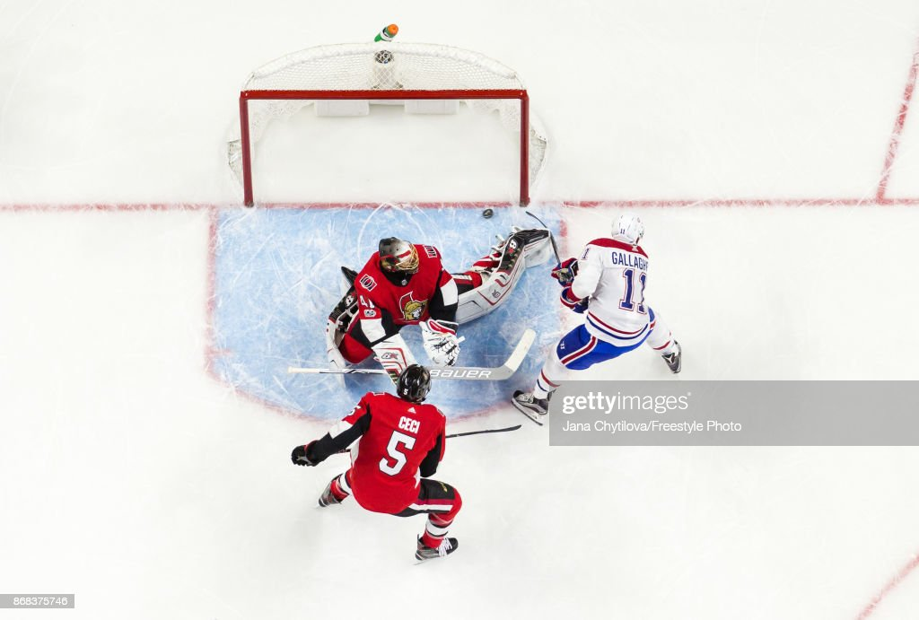 Brendan Gallagher #11 of the Montreal Canadiens squeezes the puck past the outstretched pad of Craig Anderson #41 of the Ottawa Senators as Cody Ceci #5 of the Ottawa Senators looks on in the second period at Canadian Tire Centre on October 30, 2017 in Ottawa, Ontario, Canada.