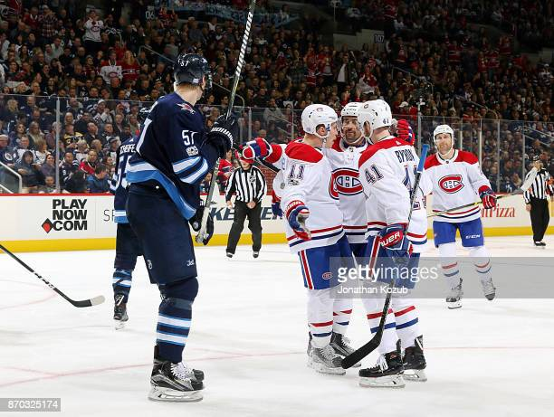 Brendan Gallagher Tomas Plekanec and Paul Byron of the Montreal Canadiens celebrate a third period goal as Tyler Myers of the Winnipeg Jets looks on...