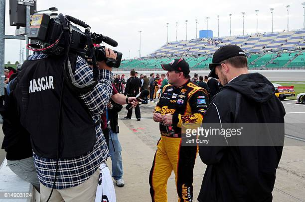 Brendan Gaughan driver of the South Point Chevrolet is interviewed on the grid after the conclusion of the NASCAR XFINITY Series Kansas Lottery 300...