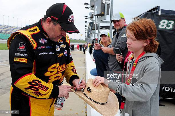 Brendan Gaughan driver of the South Point Chevrolet signs an autograph on the grid after the conclusion of the NASCAR XFINITY Series Kansas Lottery...