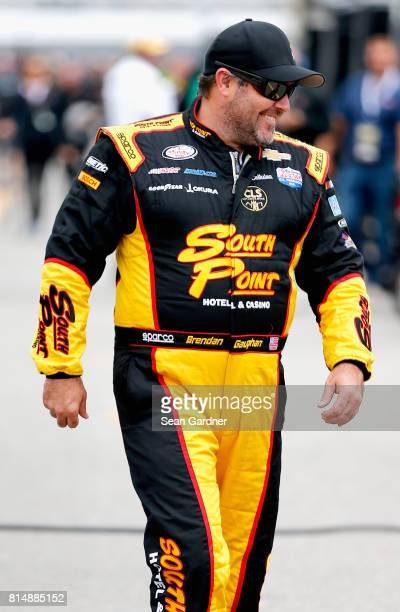 Brendan Gaughan driver of the South Point Hotel Casino Chevrolet walks down the grid during qualifying for the NASCAR XFINITY Series Overton's 200 at...