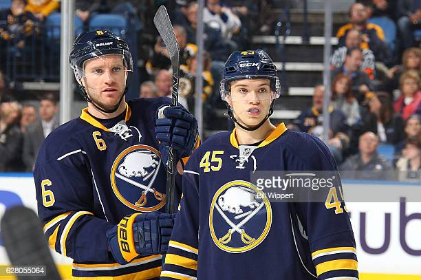 Brendan Guhle of the Buffalo Sabres stands alongside Cody Franson in Guhle's first NHL game against the Boston Bruins at the KeyBank Center on...