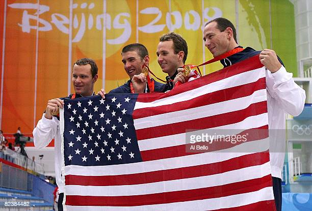 Brendan Hansen Michael Phelps Aaron Piersol and Jason Lezak of the United States hold the American Flag after receiving the gold medal in the Men's...