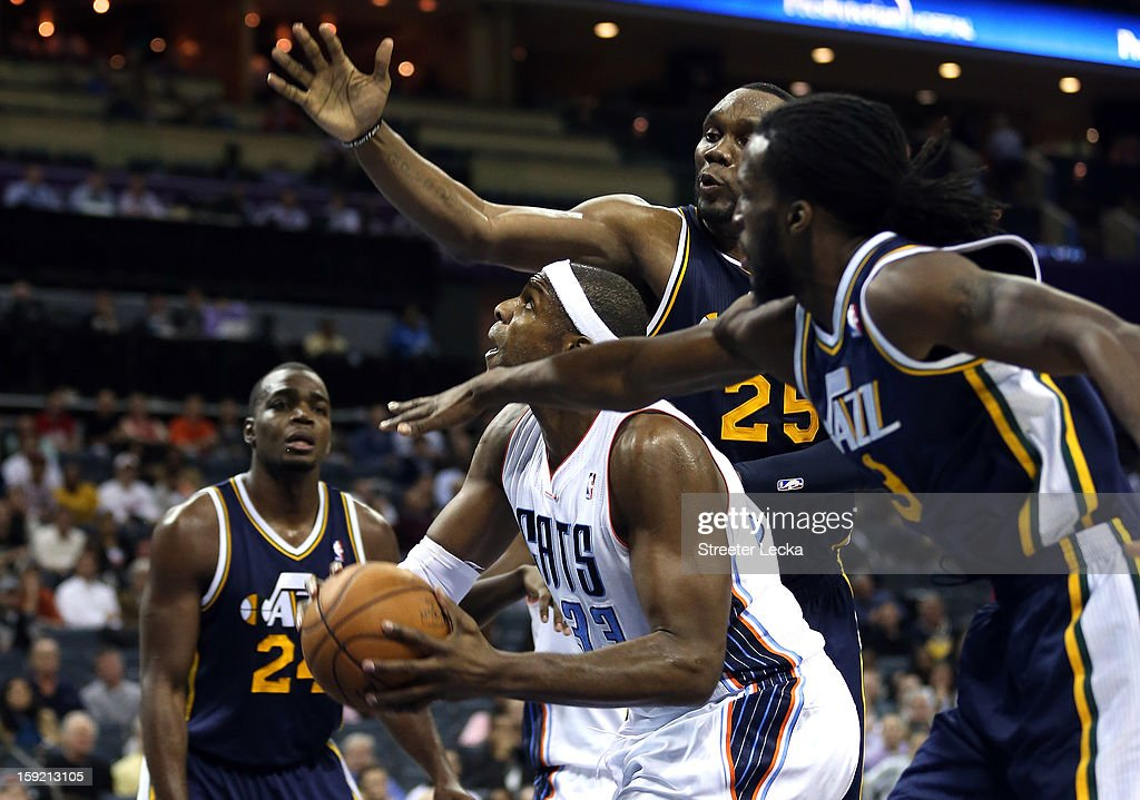 Brendan Haywood #33 of the Charlotte Bobcats goes to the basket against Al Jefferson #25 of the Utah Jazz and DeMarre Carroll #3 during their game at Time Warner Cable Arena on January 9, 2013 in Charlotte, North Carolina.