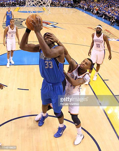 Brendan Haywood of the Dallas Mavericks goes up for a shot as Daequan Cook of the Oklahoma City Thunder grabs his face in Game Three of the Western...