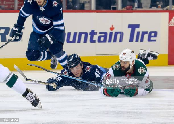 Brendan Lemieux of the Winnipeg Jets and Daniel Winnik of the Minnesota Wild fall to the ice as they chase the play during first period action at the...