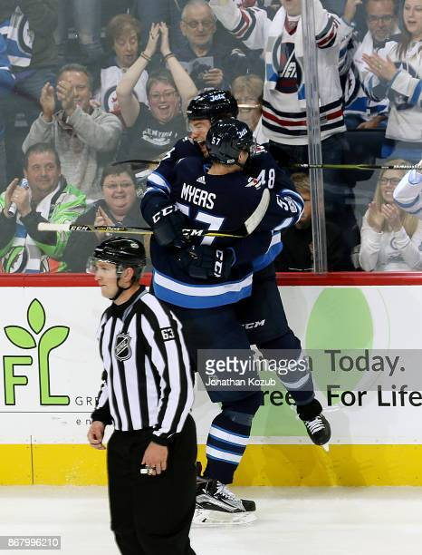 Brendan Lemieux of the Winnipeg Jets jumps into the arms of teammate Tyler Myers as they celebrate his first career NHL goal during third period...