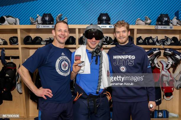 Brendan Lemieux of the Winnipeg Jets poses with teammates Matt Hendricks and Joel Armia after scoring his first career NHL goal against the...
