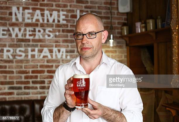 Brendan McBride manager of the The Sun Inn a Shepherd Neame Plc pub holds a pint of Master Brew ale in Faversham UK on Friday April 22 2016 Kentish...