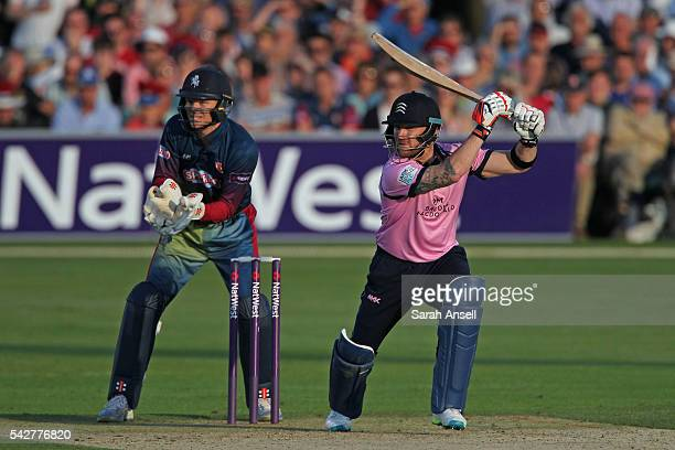 Brendan McCullum of Middlesex hits a boundary as Kent wicket keeper Sam Billings looks on during the Natwest T20 Blast match between Kent and...