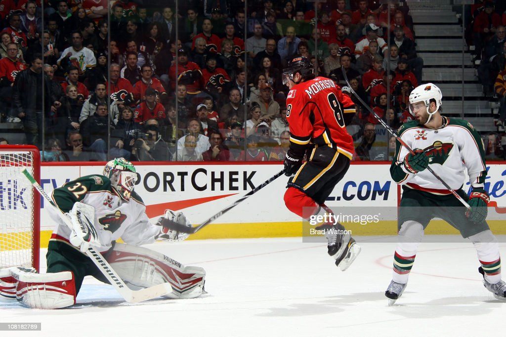 Brendan Morrison of the Calgary Flames jumps to tip a shot in front of Niklas Backstrom of the Minnesota Wild on January 19 2011 at the Scotiabank...